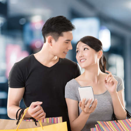 asian shopper: Young Asian couple shopping and looking at cellphone in the mall Stock Photo