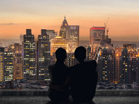 Silhouette of couple sit on ground point faraway on the roof above the city in the night. Stockfoto