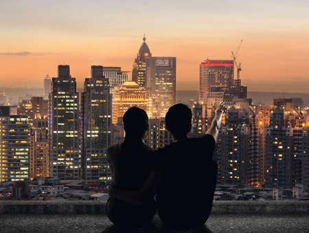 Silueta pár sedět na zemi bod dálky na střeše nad městem v noci.
