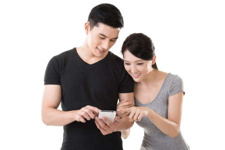 Asian young couple using cellphone, closeup portrait. Banco de Imagens