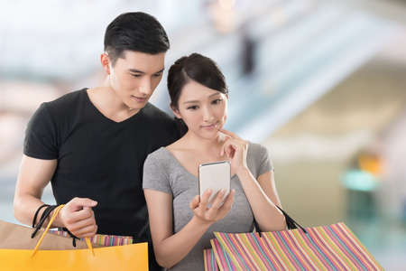holiday message: Young Asian couple shopping and looking at cellphone, closeup portrait.