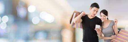 Jonge Aziatische paar winkelen en kijken naar mobiel in het winkelcentrum Stockfoto