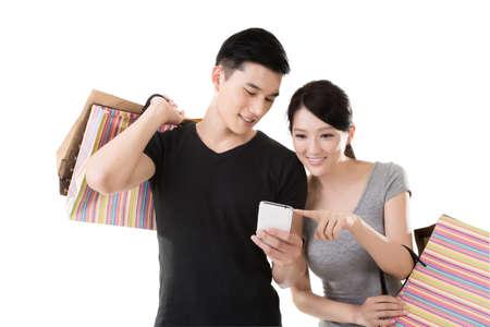 shopping: joven pareja asiática de compras y mirando móvil Foto de archivo