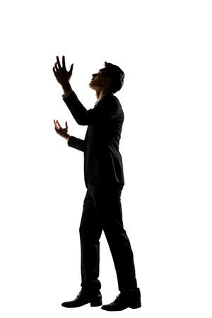 pray: Silhouette of Asian businessman praying, full length portrait isolated