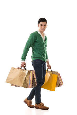 buyer: Asian young man holding shopping bags, full length portrait isolated. Stock Photo