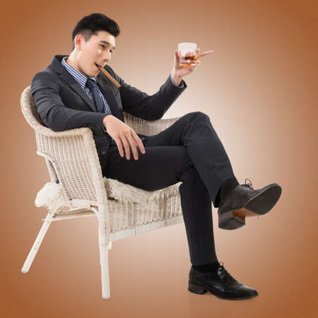 asia style: confident young Asian businessman holding a cigar