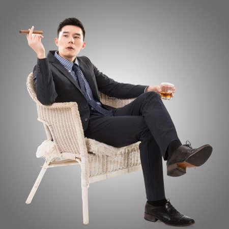 asian business man: confident young Asian businessman holding a cigar
