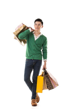 Asian young man holding shopping bags, full length portrait isolated. Foto de archivo