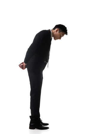 man looking down: Asian business man looking down, full length portrait isolated Stock Photo