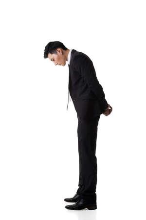 Asia hombre de negocios mirando hacia abajo, aislado retrato de cuerpo entero Foto de archivo