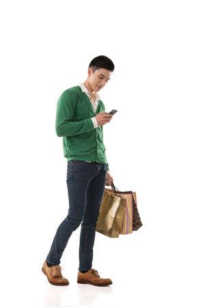 Azji młody człowiek gospodarstwa torby na zakupy i przy użyciu telefon komórkowy, Portret pełnej długości samodzielnie. Zdjęcie Seryjne