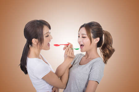 asian group: Asian woman with her friend play with spoon. Stock Photo