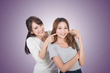 women smiling: Asian woman with her friend, studio shot portrait.