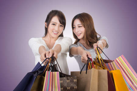 happy customer: Asian shopping woman with her friends holding bags.