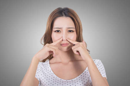 nose: Portrait of a young woman holding her nose because of a bad smell.