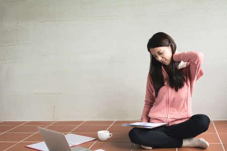 Donna asiatica che lavora a casa e sentirsi stanco. Archivio Fotografico - 52188196
