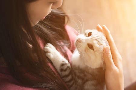 Asijské žena hrát si s ní kotě doma.