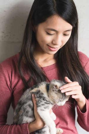 Eine asiatische Frau mit ihrem Kätzchen zu Hause spielen.