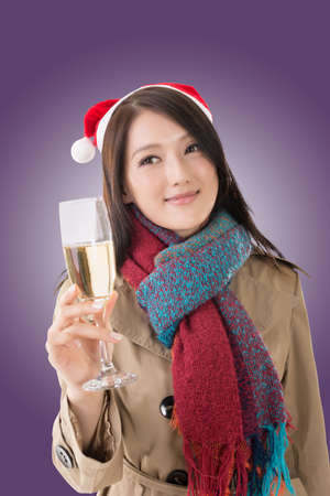 christmas hats: Smiling Asian woman hold a glass of champagne and look at you in a Christmas party, closeup portrait Stock Photo