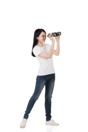 opportunity discovery: woman using binoculars, studio shot portrait