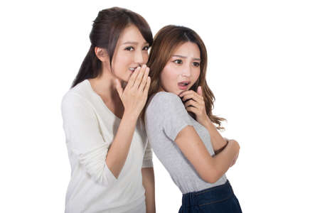 whisper: Asian friends whisper, full length portrait.