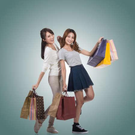 chicas de compras: Sonrisa feliz de muchachas de compras de bolsas asiáticas que se sostienen con sus amigos. Foto de archivo