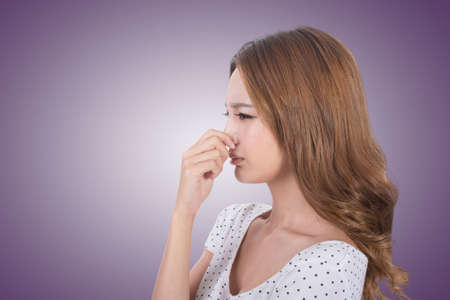 human nose: Portrait of a young woman holding her nose because of a bad smell.