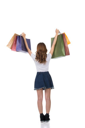 view woman: Rear view of Asian shopping woman holding bags, full length portrait isolated.