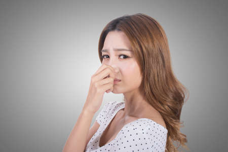 bad: Portrait of a young woman holding her nose because of a bad smell.