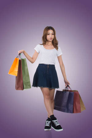 asian shopper: Smiling happy Asian woman shopping and holding bags, full length portrait isolated. Stock Photo
