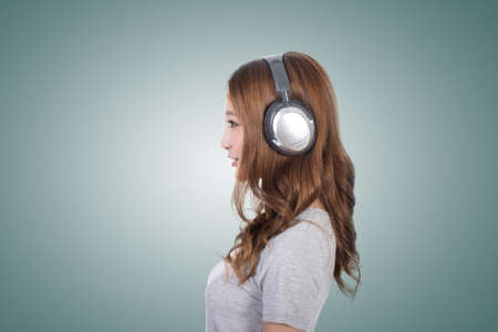 asian style: Woman enjoy the music by using earphones.