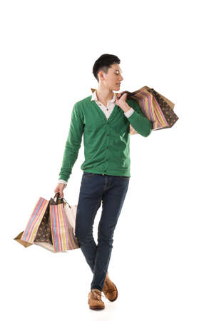 handsome young man: Asian young man holding shopping bags, full length portrait isolated. Stock Photo