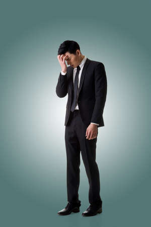 Regret young business man standing and thinking, full length portrait isolated Stock Photo