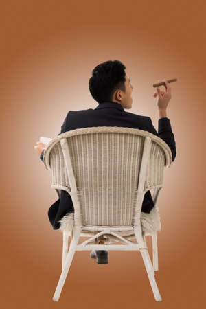 tricky: Cunning businessman of Asian sit on chair.