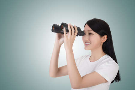 woman searching: woman using binoculars, studio shot portrait