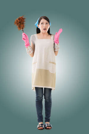 housewife gloves: Portrait of Asian housewife using feather duster, full length portrait