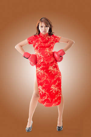 chipao: Smiling Chinese woman dress traditional cheongsam at New Year, studio shot isolated. Stock Photo