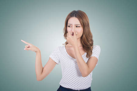 oler: Retrato de una mujer joven con su nariz debido a un mal olor.