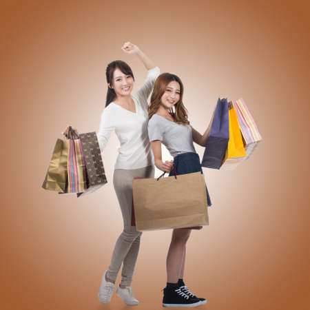korean girl: Happy smiling shopping girls of Asian holding bags with her friends. Stock Photo