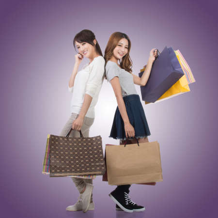 two sexy women: Happy smiling shopping girls of Asian holding bags with her friends. Stock Photo