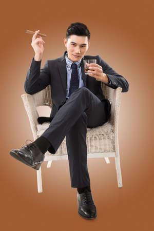 persona sentada: seguros de negocios asiático joven que sostiene un cigarro
