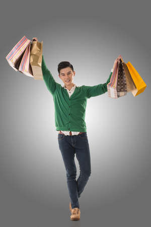 asia people: Asian young man holding shopping bags, full length portrait isolated. Stock Photo
