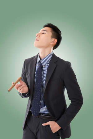 young businessman: confident young Asian businessman holding a cigar