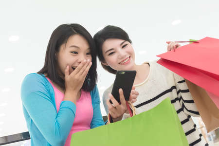 excite: Excite women go shopping and use a smartphone in department store Stock Photo