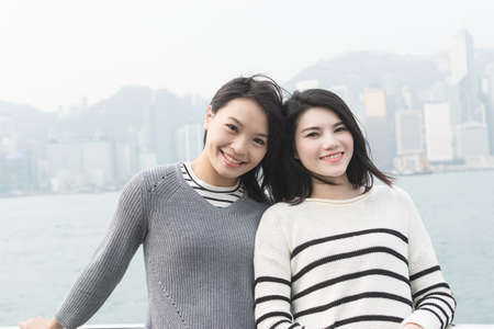 people together: Asian happy young girls traveling at Victoria harbor, Hong Kong, Asia. Stock Photo