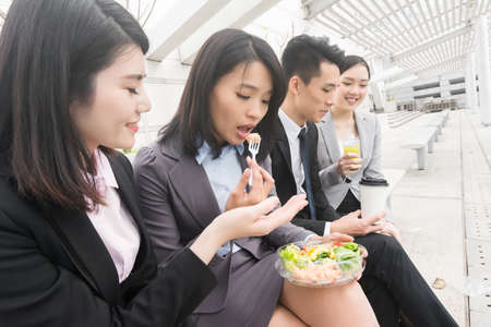 break from work: group of Asian business team having lunch in the outdoor