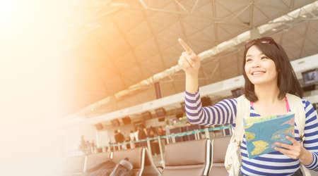 공항에서 아시아 젊은 여성이 항공기를 기다립니다 스톡 콘텐츠 - 56952294