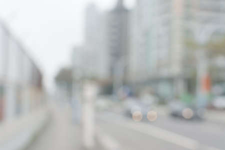 blurred people: Abstract urban background with blurred buildings and street, shallow depth of focus.