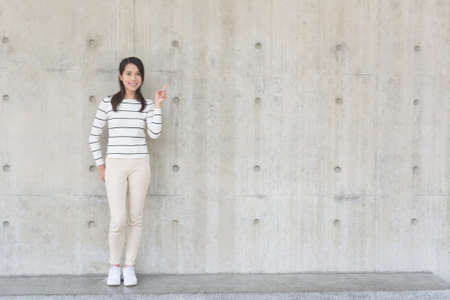 thinking woman: Woman thinking against concrete wall Stock Photo