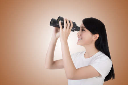 using binoculars: woman using binoculars, studio shot portrait